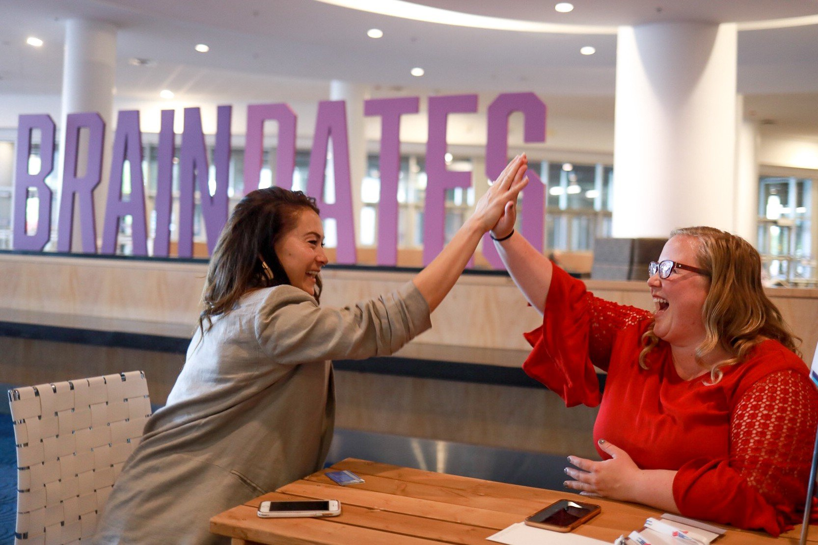 Two women high fiving at NAA Apartmentalize
